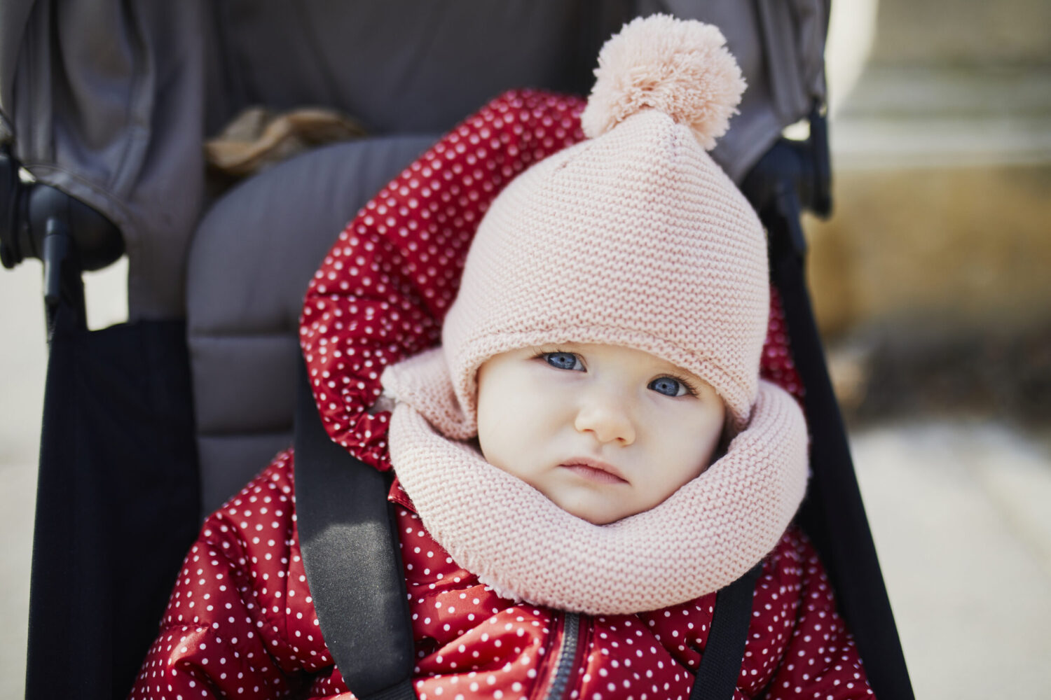 Adorable little girl in red jacket and pink knitted hat sitting in pushchair outdoors on a fall day. Autumn walks with kids